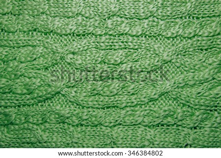 Wool sweater or scarf texture close up. Knitted jersey background with a relief pattern. Braids in machine knitting pattern. Wool hand-knitted or machine knitting pattern. Closeup Fabric Background - stock photo