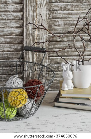 Wool yarn in a vintage basket, books and easter bunny on rustic light wood table. Still life in vintage and rustic style - stock photo