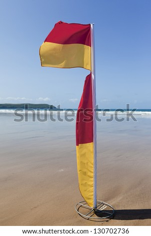 WOOLACOMBE, UK - MAY 19: Red and yellow safety flag fluttering in the wind on Woolacombe beach in North Devon on 19th May 2011. The flag is used by the lifeguards to mark the safe swimming area.