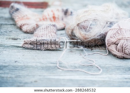 Woolen thread with incomplete knitting socks on vintage wooden background - stock photo