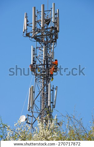 WORCESTER,UK - APRIL 14 2015 : Maintenance workers carry out repairs high up on a communications tower using safety equipment - stock photo