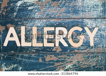 Word allergy written on rustic wooden surface