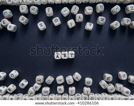 Word Art of small white cubes next to a bunch of other letters on the surface of the composition on a dark background
