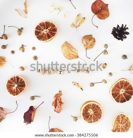 "Word ""Autumn"", fried oranges and yellow leaves at white background. Flat lay - stock photo"
