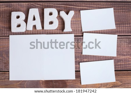 word baby and white frame photo on wood background - stock photo