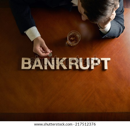 Word Bankrupt made of wooden block letters and devastated middle aged caucasian man in a black suit sitting at the table with the glass of whiskey, top view composition with dramatic lighting - stock photo