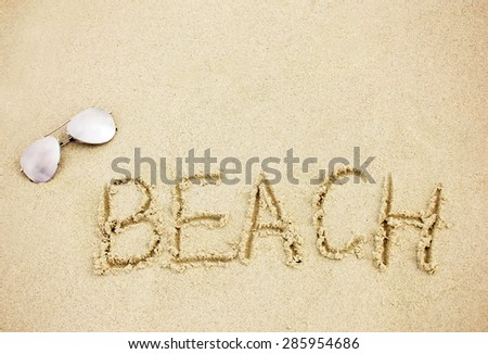 Word beach on the sandy beach with sunglasses - stock photo