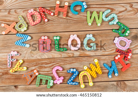 Word BLOG letters on old wooden board background.