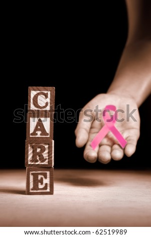 Word 'Care' from wooden block with hand holding pink ribbon on dark background - stock photo