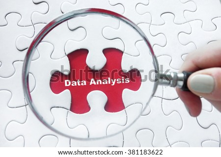 Word Data Analysis with hand holding magnifying glass over jigsaw puzzle - stock photo