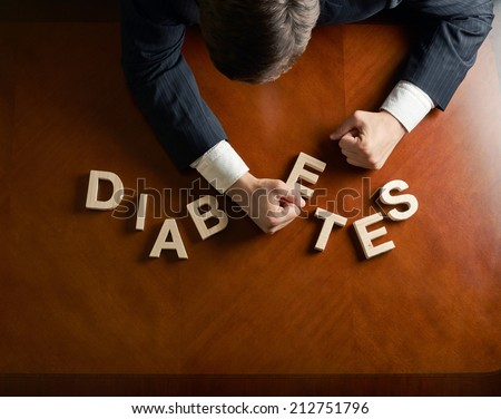 Word Diabetes made of wooden block letters and devastated middle aged caucasian man in a black suit sitting at the table, top view composition with dramatic lighting - stock photo