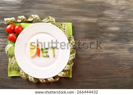 Word DIET made of sliced vegetables in plate with measuring tape on wooden table, top view - stock photo