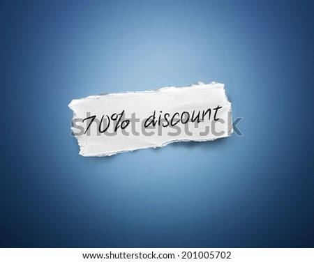 Word - 70% discount - written on a torn rectangular scrap of white paper on a blue background with a vignette - stock photo
