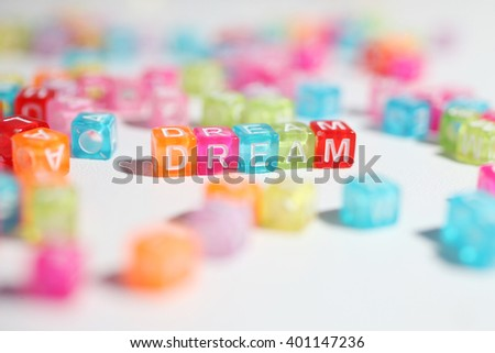 Word dream of multicolor cubes and blurred cubes with letters around  - stock photo