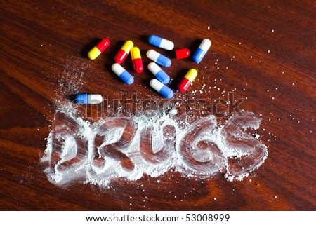 Word drugs written on powder with medicines on table. - stock photo