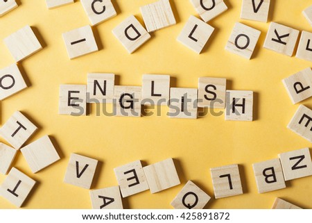 Word english made with block wood letters next to a pile of other letter over wooden table. - stock photo