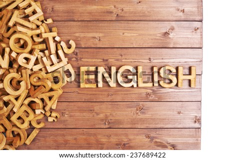 Word english made with block wooden letters next to a pile of other letters over the wooden board surface composition - stock photo