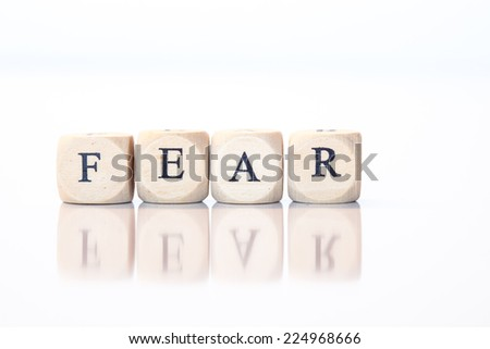 Word Fear spelled from single dice letters, with reflection on bottom - stock photo