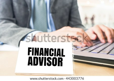 word financial advisor white card on blurred business man using computer laptop office desk background - stock photo