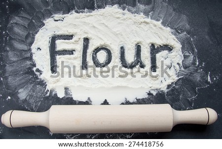 Word Flour Written on Flour on Black Background and rolling pin - stock photo