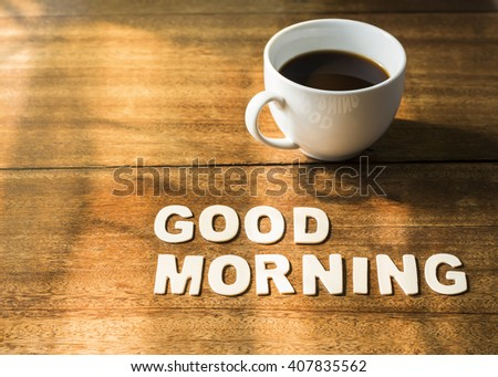 "word  ""Good morning"" design by white letter press near a coffee cup and book with window light in the morning on wooden background - stock photo"