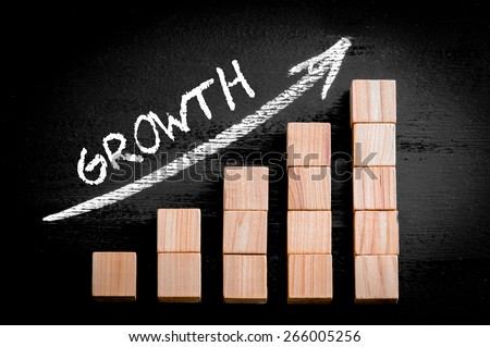 Word Growth on ascending arrow above bar graph of Wooden small cubes isolated on black background. Chalk drawing on blackboard. Business Concept image. - stock photo