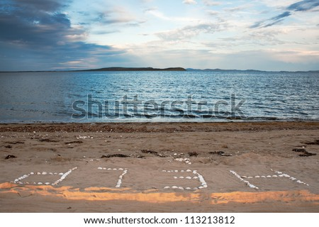 "Word ""Help"" from sea cockleshells on the sand - stock photo"