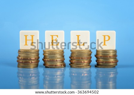 Word HELP on stacked coins, finance conceptual.