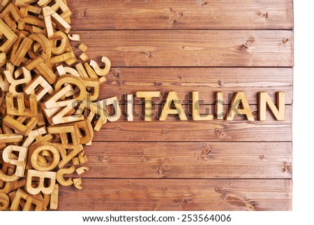Word italian made with block wooden letters next to a pile of other letters over the wooden board surface composition