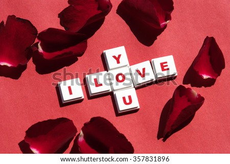"Word letters spelling out the word ""I Love You"" on red rose petals on red paper background, selective focus - stock photo"