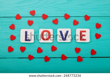 Word love and hearts on blue wooden background - stock photo