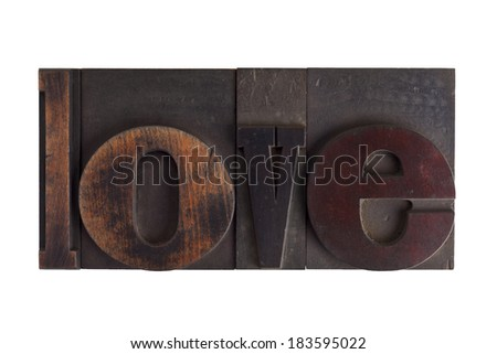 Word love in vintage wooden letterpress type, scratched and stained, isolated on white background - stock photo
