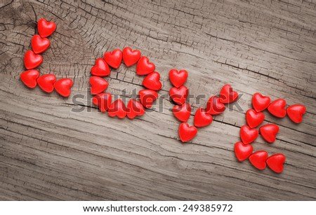 "Word ""LOVE"" laid out from candy in heart shape on wooden background. Valentine's Day"