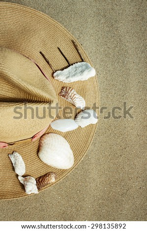 Word love made out of small sea shells on a side of a summer straw hat on the beach. - stock photo