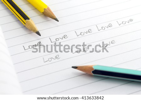word Love on notebook and pencil