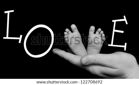 Word LOVE with Baby legs. Legs newborn on a black background - stock photo