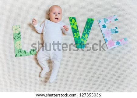 Word LOVE with cute lying baby boy. - stock photo