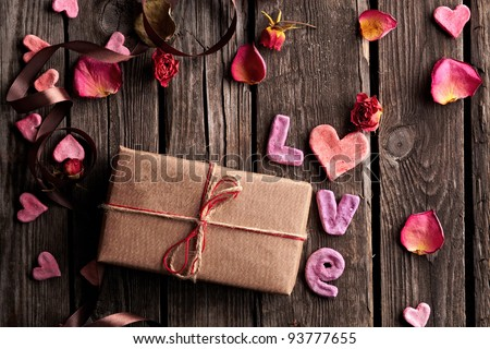 Word Love with gift box on old vintage wooden plates. Sweet holiday background - rose petals, small hearts, curved ribbon, etc.
