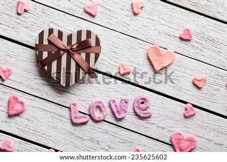 Word Love with heart shaped gift box on old white wooden plates. Sweet holiday background. - stock photo