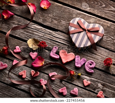 Word Love with Heart shaped Valentines Day gift box on old vintage wooden plates. - stock photo