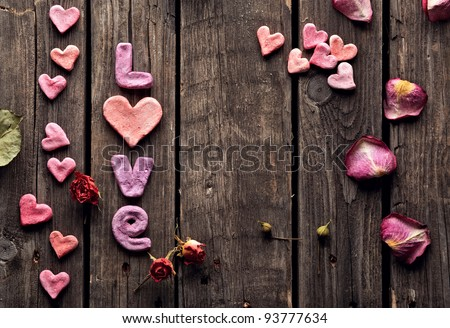 Word Love with rose petals and small heart shaped stuff on old vintage wood plates. Sweet holiday background. - stock photo
