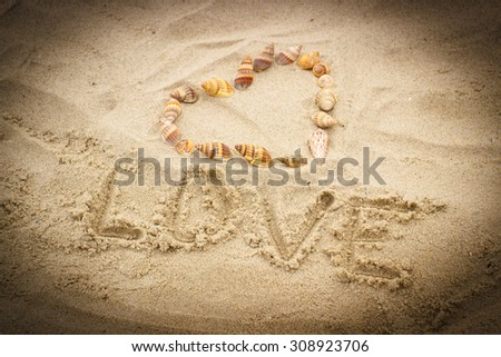 Word love written on sand at the beach and heart of shells, symbol of love, summer time - stock photo