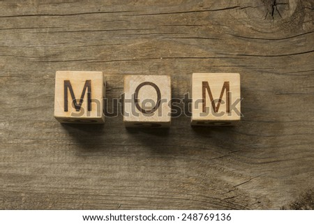 Word MOM on the child blocks on a wooden background - stock photo