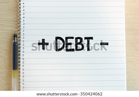 "Word of "" + debt - "" in white note with black pen on the background of wood. - stock photo"