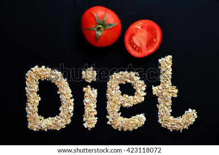 Word of oatmeal. Diet. Diet healthy food. A healthy breakfast of oatmeal. Ripe tomatoes near oatmeal. Black background - stock photo