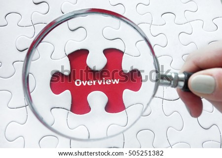 Word Overview with hand holding magnifying glass over jigsaw puzzle