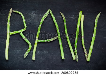 Word Raw made of asparagus vegetables on black wooden board, top view.  Healthy food concept. - stock photo
