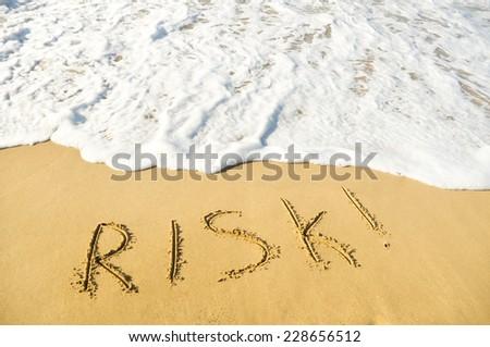 """Word """"risk"""" written on sea sand - stock photo"""