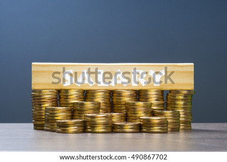 Word salary with multiple stacked gold coins on dark background.
