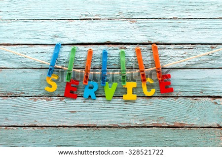 word service fasten clothespins on a rope behind a wooden background - stock photo